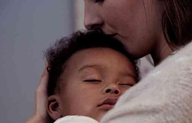 Μητέρα με γιο ύπνο στην αγκαλιά της